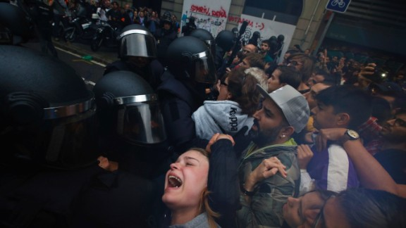 People clash with Spanish National Police outside the Ramon Llull school, designated as a polling station by the Catalan government in Barcelona, Spain, early Sunday, October 1. Catalan pro-referendum supporters vowed to ignore a police ultimatum to leave the schools they are occupying to use in a vote seeking independence from Spain.