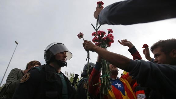 People try to offer flowers to a civil guard at the entrance of a sports center, assigned to be a referendum polling station by the Catalan government in Sant Julia de Ramis, near Girona, Spain, October 1.