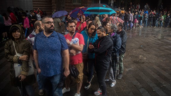 People queue to vote at a school in Barcelona.