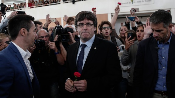 """Catalan President Carles Puigdemont, center, arrives to inspect a sports hall as police interve in Girona, Spain. Puigdemont condemned """"indiscriminate aggression"""" against peaceful voters."""