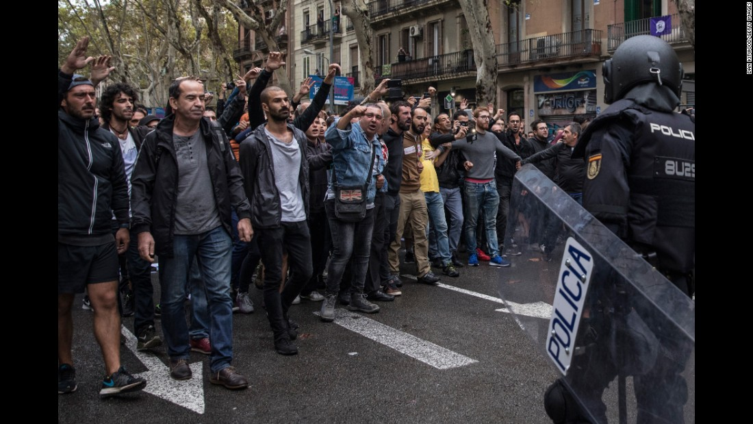 Pro-referendum supporters clash with members of the Spanish National Police after police tried to enter a polling station to retrieve ballot boxes.