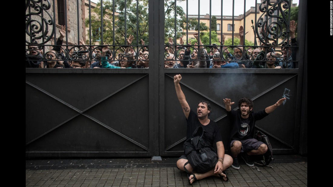 Pro-referendum supporters lock a gate to a polling station as members of the Spanish National Police arrive to control the area during voting at the Escola Industrial of Barcelona.