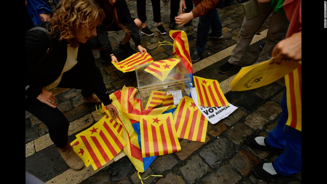 Pro-independence supporters cover a mock ballot box with Estelada Catalan flags in Pamplona, northern Spain.