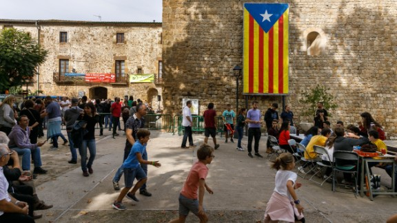 People play games in a square where a giant pro-independence Estelada Catalan flag is displayed.