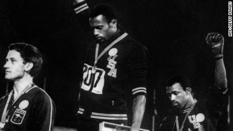 """Forty years after Tommie Smith and John Carlos raised their fists in a civil rights gesture on the Olympic medal stand in Mexico City, protests on the podium could make a comeback in Beijing."". (FILES) US athletes Tommie Smith (C) and John Carlos (R) raise their gloved fists in the Black Power salute to express their opposition to racism in the USA during the US national anthem, after receiving their medals 17 October 1968 for first and third place in the men's 200m event at the Mexico Olympic Games. At left is Peter Norman of Australia who took second place."