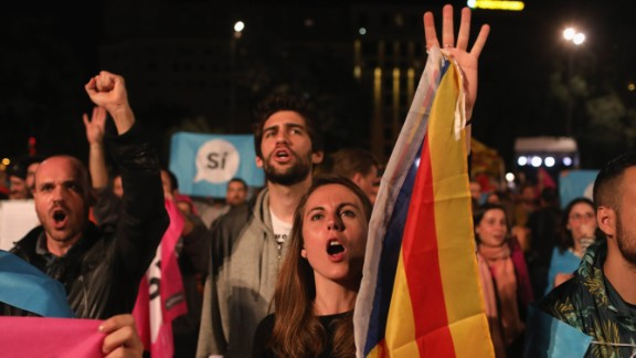 A woman holds a Catalan flag as crowds listen to Catalan President Carles Puigdemont speak via a televised press conference as they await the result of the Indepenence Referendum at the Placa de Catalunya on October 1 in Barcelona.