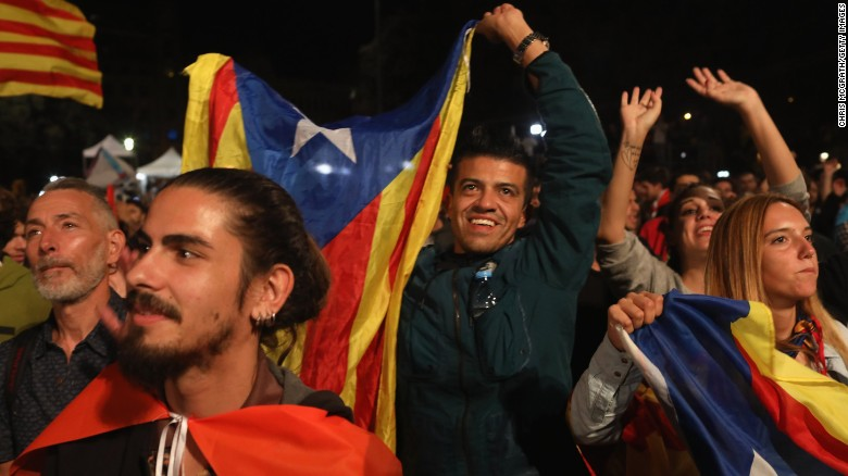 People hold Catalan flags as they listen to Catalan President Carles Puigdemont speak via a televised press conference as they await the result of the Indepenence Referendum at the Placa de Catalunya on October 1 in Barcelona, Spain.