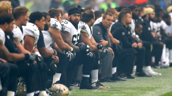 The New Orleans Saints team kneels before standing for the National Anthem in a game against the Miami Dolphins in London's Wembley Stadium.
