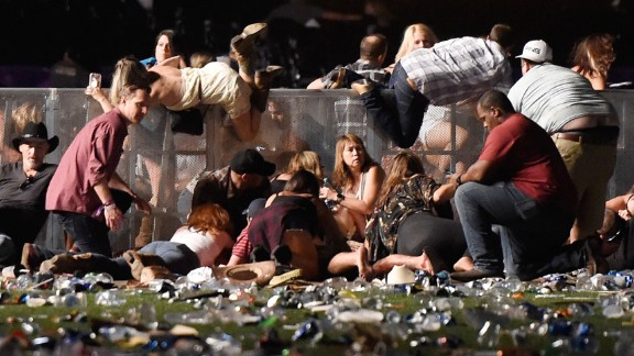 People scramble for cover at the Route 91 Harvest country music festival after gun fire was heard on  October 1, 2017 in Las Vegas, Nevada.