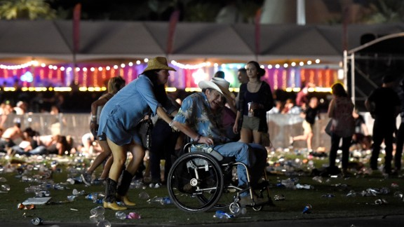 A man in a wheelchair is evacuated from the festival after gunfire was heard.