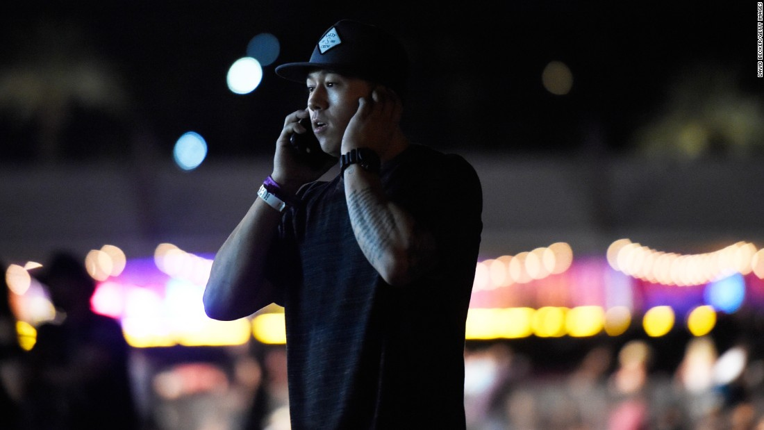 A man makes a phone call as people run from the festival grounds.