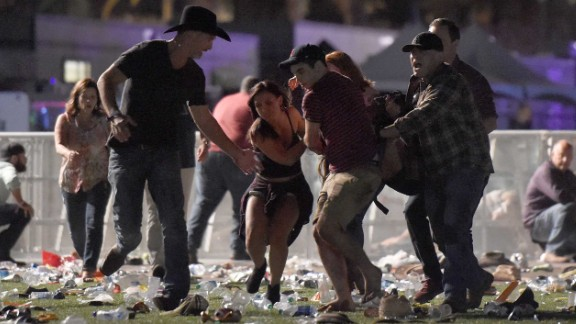 Concertgoers help an injured person at the scene.