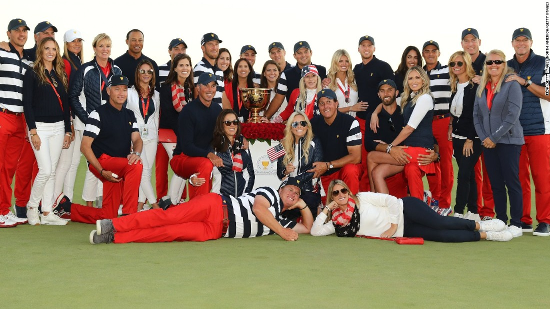 The US players and their wives and partners pose with the trophy after victory was assured.