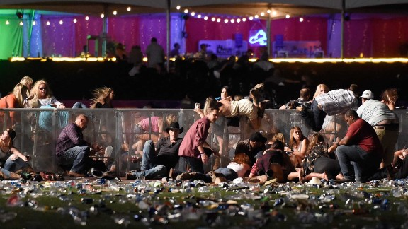 Concertgoers dive over a fence to take cover from gunfire on Sunday night.