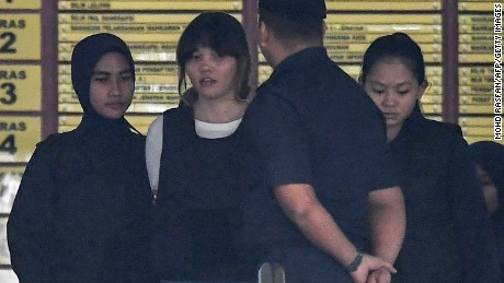 Police escort Vietnamese defendant Doan Thi Huong (2nd left) after her trial on October 2.