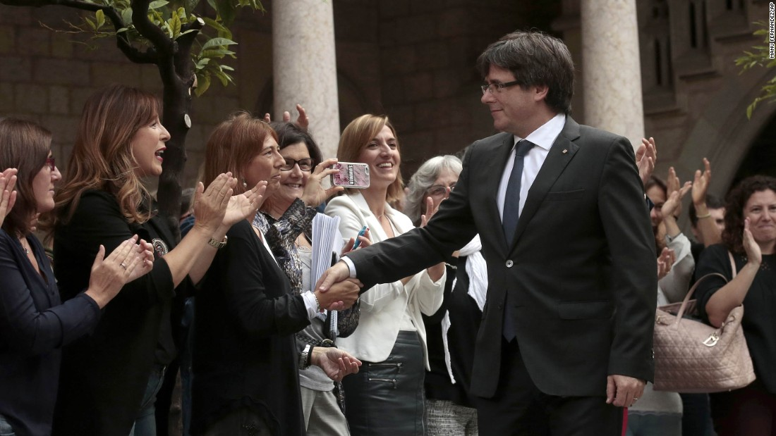 Catalan President Carles Puigdemont greets regional government workers before a meeting at the Palace of the Generalitat in Barcelona on October 2.