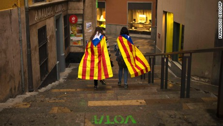 Women walk in the old quarter of Girona, Spain, draped in Catalonia's independence flag.