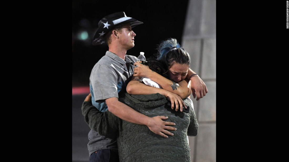 People embrace outside the Thomas & Mack Center after the shooting.