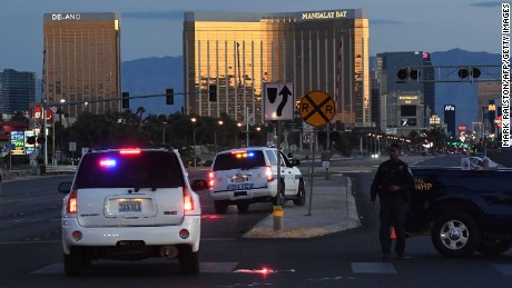 "Police form a perimeter around the road leading to the Mandalay Hotel (background) after a gunman killed at least 50 people and wounded more than 400 others when he opened fire on a country music concert in Las Vegas, Nevada on October 2, 2017.  The gunman who opened fire on concertgoers from 32nd floor of a Las Vegas hotel was found dead, apparently of a self-inflicted gunshot wound, when a police SWAT team burst in, authorities said Monday.They said at least eight weapons, including a number of long rifles, were found in the room from where 64-year-old Stephen Paddock rained automatic fire into thousands of terrified people attending a country music concert across the street.""We believe the individual killed himself prior to our entry,"" Las Vegas Sheriff Joseph Lombardo said.  / AFP PHOTO / Mark RALSTON        (Photo credit should read MARK RALSTON/AFP/Getty Images)"