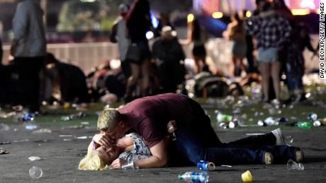 LAS VEGAS, NV - OCTOBER 01:  A man lays on top of a woman as others flee the Route 91 Harvest country music festival grounds after a active shooter was reported on October 1, 2017 in Las Vegas, Nevada. The photographer saw the woman get up and leave the scene.