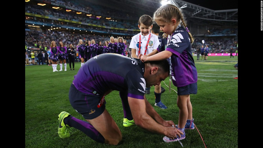 Melbourne captain Cameron Smith ties his daughter's shoelaces after his team won the grand final of the National Rugby League on Sunday, October 1. The Storm defeated North Queensland 34-6 in Sydney.