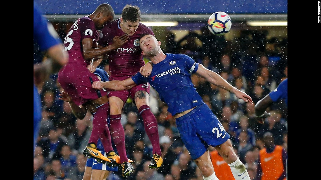 Chelsea's Gary Cahill, right, goes up for a header with Manchester City players Fernandinho and John Stones during a Premier League match in London on Saturday, September 30.
