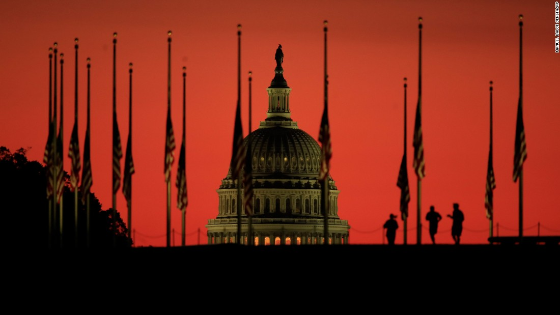 American flags stand at half-staff as the sun rises over Washington on October 3.