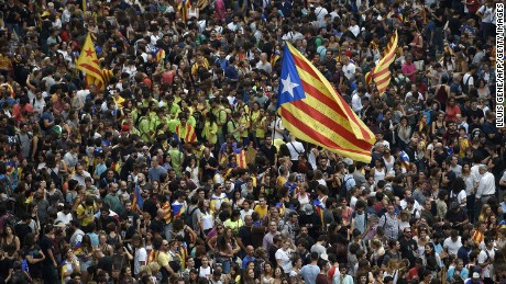 Protesters wave a Catalan pro-independence 'Estelada' flag as they gather at the Placa de la Universitat square in Barcelona during a general strike in Catalonia called by Catalan unions on October 3, 2017.