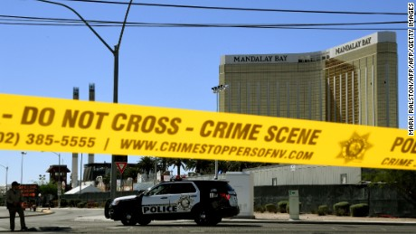 TOPSHOT - Crime scene tape surrounds the Mandalay Hotel (background with shooters window damage top right) after a gunman killed at least 58 people and wounded more than 500 others when he opened fire on a country music concert in Las Vegas, Nevada on October 2, 2017.  Police said the gunman, a 64-year-old local resident named as Stephen Paddock, had been killed after a SWAT team responded to reports of multiple gunfire from the 32nd floor of the Mandalay Bay, a hotel-casino next to the concert venue. / AFP PHOTO / Mark RALSTON        (Photo credit should read MARK RALSTON/AFP/Getty Images)