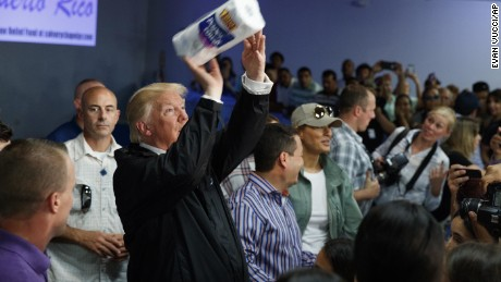 President Donald Trump tosses paper towels into a crowd as he hands out supplies at Calvary Chapel, Tuesday, Oct. 3, 2017, in Guaynabo, Puerto Rico. Trump is in Puerto Rico to survey hurricane damage. (AP Photo/Evan Vucci)