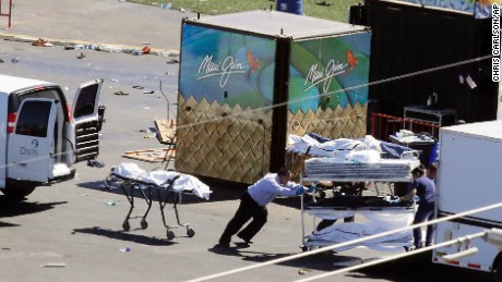 Investigators load bodies from the scene of a mass shooting at a music festival near the Mandalay Bay resort and casino on the Las Vegas Strip on Monday, Oct. 2, 2017, in Las Vegas. (AP Photo/Chris Carlson)