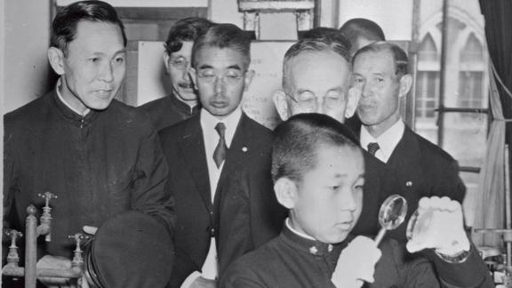 Akihito, 14, uses a magnifying glass at the Peers School in Tokyo. At about the age of 5, Akihito was separated from his parents, in accordance with Japanese custom at the time, and raised and educated by chamberlains and tutors.