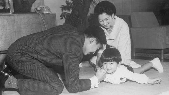 Akihito arm-wrestlers Naruhito while Michiko looks on. The couple had another son, Fumihito, in 1965. Their only daughter, Sayako, was born in 1969.