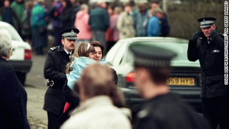 A young girl is carried away from the Dunblane primary school in Scotland shortly after the shooting in 1996.
