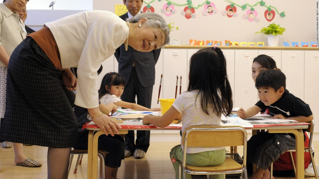 Japanese Empress Michiko, left, chats with a girl while watching children draw pictures at a daycare center in Tokyo on May 15, 2009.