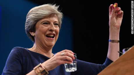 Britain's Prime Minister Theresa May holds up a throat sweet given to her by Britain's Chancellor of the Exchequer Philip Hammond as she delivers her speech on the final day of the Conservative Party annual conference at the Manchester Central Convention Centre in Manchester, northwest England, on October 4, 2017. / AFP PHOTO / Oli SCARFF        (Photo credit should read OLI SCARFF/AFP/Getty Images)