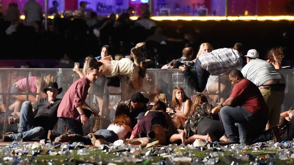People scramble after gunfire strikes the Route 91 Harvest country music festival in Las Vegas.