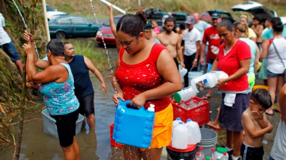 People collect water from a natural spring created by the landslides in a mountain next to a road in Corozal, west of San Juan, Puerto Rico, on September 24, 2017.