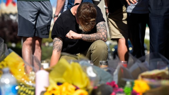 LAS VEGAS, NV - OCTOBER 04:  Bry Thompson, 21, of Las Vegas kneels at a makeshift memorial set up across from the Las Vegas Village on October 4, 2017 in Las Vegas, Nevada. Thompson had friends attending the Route 91 Harvest country music festival when a lone gunman opened fire on the crowd killing at least 59 people and injuring more than 500. The massacre is one of the deadliest mass shooting events in U.S. history. Thompson's friends were unhurt.  (Photo by David Becker/Getty Images)