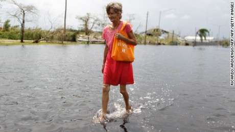 A woman wades through a flooded street in the aftermath of Hurricane Maria in Catano, Puerto Rico, on September 22, 2017. Puerto Rico battled dangerous floods Friday after Hurricane Maria ravaged the island, as rescuers raced against time to reach residents trapped in their homes and the death toll climbed to 33. Puerto Rico Governor Ricardo Rossello called Maria the most devastating storm in a century after it destroyed the US territory's electricity and telecommunications infrastructure.  / AFP PHOTO / Ricardo ARDUENGO        (Photo credit should read RICARDO ARDUENGO/AFP/Getty Images)