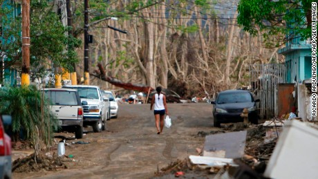 A woman walks on a road affected by the Hurricane Maria passing in Toa Baja, Puerto Rico on October 5, 2017.  US President Donald Trump asks Congress for a bumper $29 billion package of emergency relief after Hurricane Maria slammed into Puerto Rico. / AFP PHOTO / Ricardo ARDUENGO        (Photo credit should read RICARDO ARDUENGO/AFP/Getty Images)