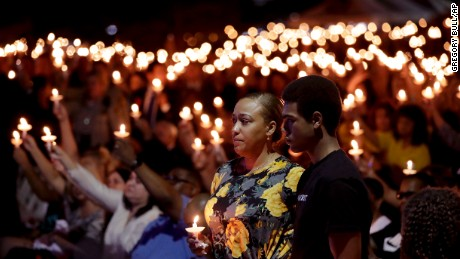 Veronica Hartfield, stands with her son, Ayzayah during a candlelight vigil for her husband, Charleston.