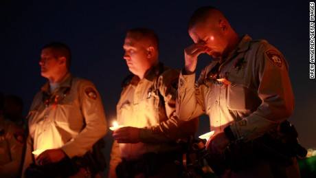 LAS VEGAS, NV - OCTOBER 5: Police officer colleagues of Las Vegas Metropolitan Police Department Officer Charleston Hartfield hold candles during a vigil for Hartfield at Police Memorial Park on October 5, 2017 in Las Vegas, Nevada. Hartfield, who was off duty at the Route 91 Harvest country music festival on October 1, was killed when Stephen Paddock opened fire on the crowd killing at least 58 people and injuring more than 450. The massacre is one of the deadliest mass shooting events in U.S. history. (Photo by Drew Angerer/Getty Images)
