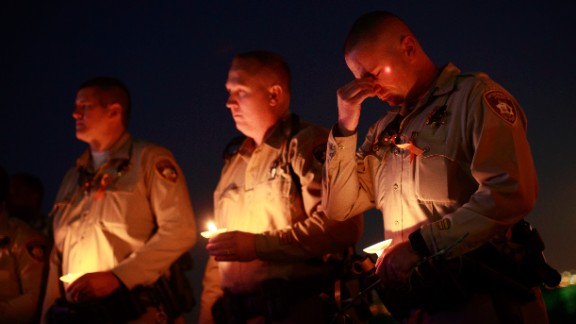 Colleagues of Las Vegas Metropolitan Police Department Officer Charleston Hartfield hold candles during a vigil for Hartfield at Police Memorial Park on October 5, 2017.