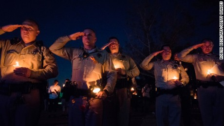 Las Vegas police officers salute during Thursday's candlelight vigil.