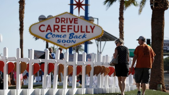 People near Las Vegas' famous sign walk by the row of crosses created by retired carpenter Greg Zanis.