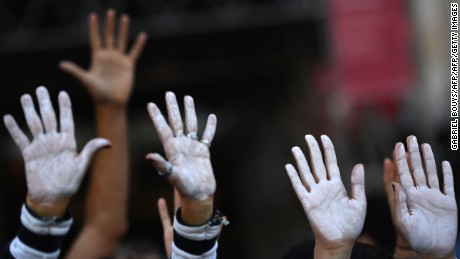 People show their hands painted in white during a demonstration Saturday in Madrid urging dialogue.