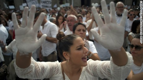 A woman shows her hands painted in white at a rally Saturday in Barcelona calling for dialogue.