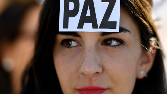 """A woman wears a sticker with the Spanish word for """"peace"""" at a demonstration in Madrid on October 7."""