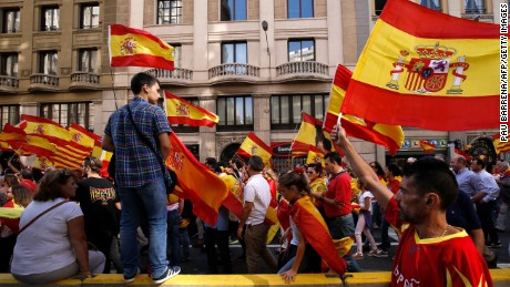 "Protesters hold Spanish flags during a demonstration called by ""Societat Civil Catalana"" (Catalan Civil Society) to support the unity of Spain on October 8, 2017 in Barcelona. Ten of thousands of flag-waving demonstrators packed central Barcelona to rally against plans by separatist leaders to declare Catalonia independent following a banned secession referendum. Catalans calling themselves a ""silent majority"" opposed to leaving Spain broke their silence after a week of mounting anxiety over the country's worst political crisis in a generation.  / AFP PHOTO / PAU BARRENA        (Photo credit should read PAU BARRENA/AFP/Getty Images)"